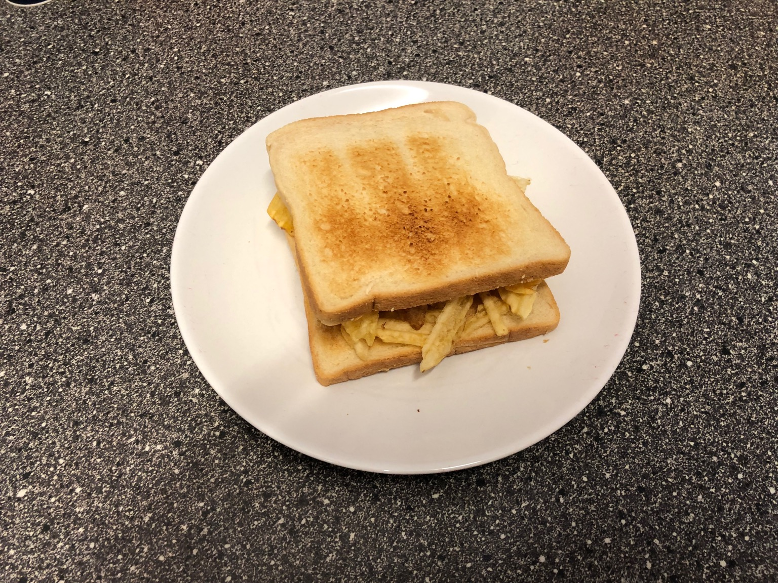 Crinkle-cut crisps between slices of white toast
