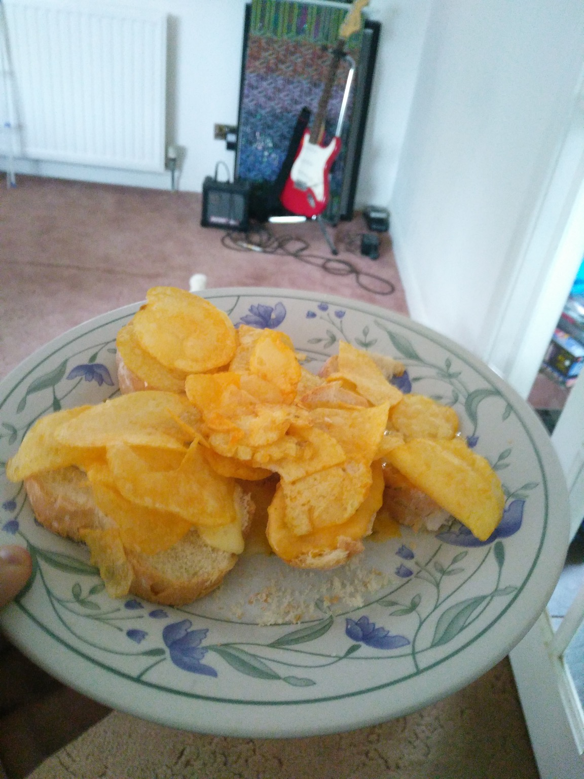 Crisps on white bread approaching a guitar
