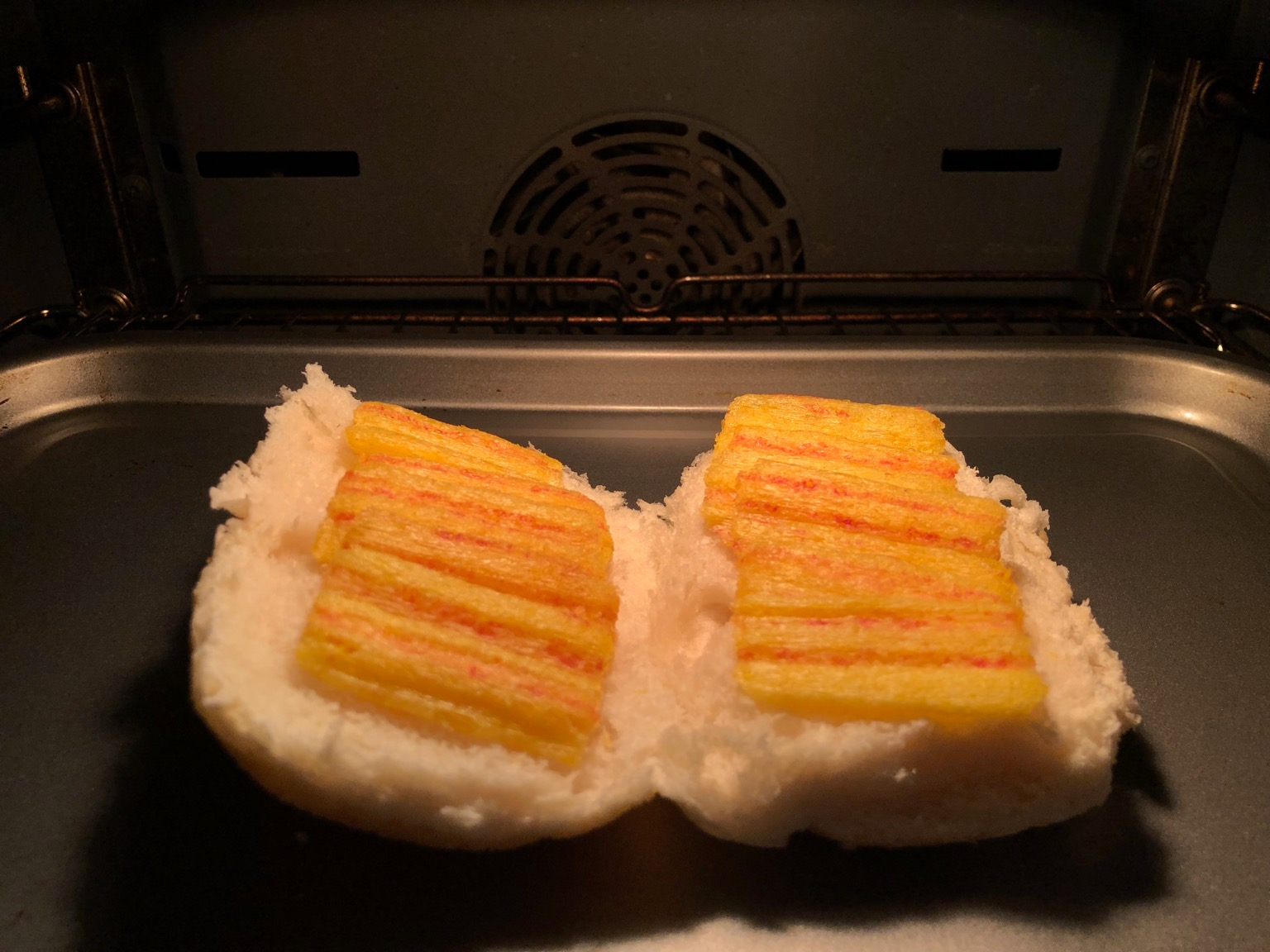 Frazzles on an open white roll in an oven